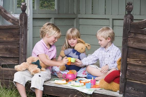 Copii ce se joaca imaginandu-se ca sunt la o Tea Party