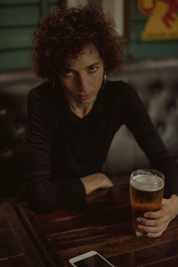 Femeie ce are in fata un pahar cu bere