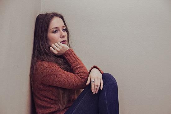 Femeie deprimata, stand rezemata de un perete