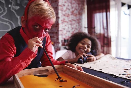Baietel pictat pe fata ce sufla intr-un pai sa deplaseze paianjeni