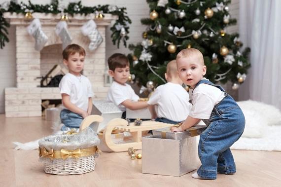 Baietel ce incearca sa scoata cadoul dintr-o cutie de cadouri