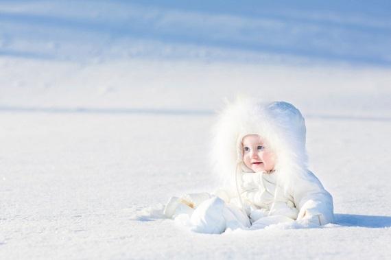 Bebelus imbracat in alb, in zapada