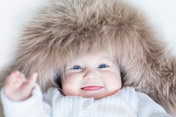 Bebelus ce poarta o caciula mare de blana