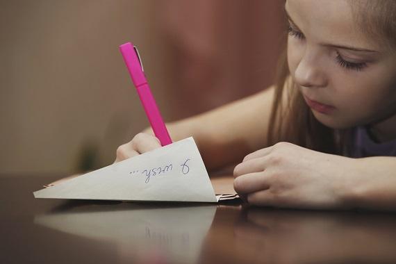 Fetita ce scrie o scrisoare