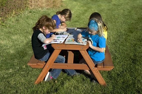 Copii ce desfasoara diferite activitati la o masuta de picnic