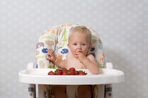 Bebelus ce sta in scaunelul sau si mananca niste capsuni
