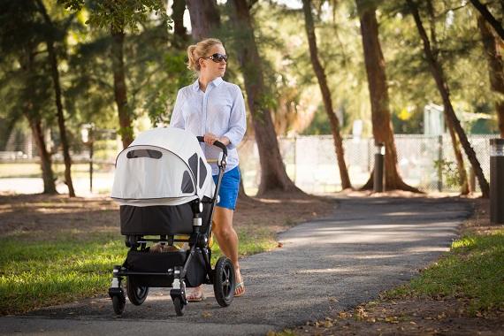 Mama ce isi plimba bebelusul in carucior intr-un parc