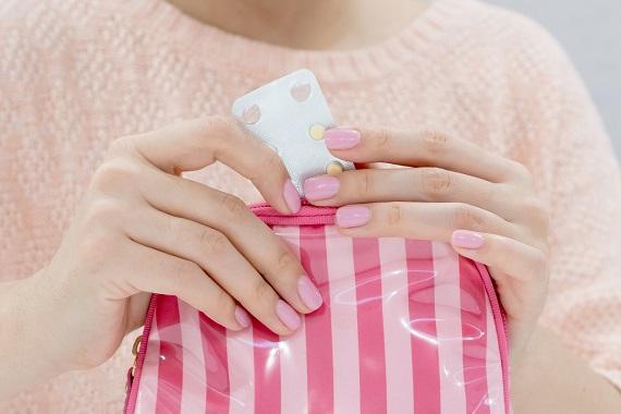 Femeie ce scoate dintr-un portofel un blister cu pastile