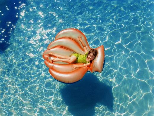 Fetita ce se afla pe o saltea, in piscina