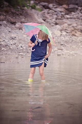 Fetita cu umbrela si cu cizmulite de cauciuc