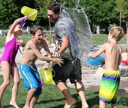 Grup de copii ce se joaca cu apa