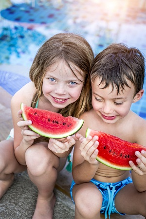 Copii ce mananca pepene, la piscina