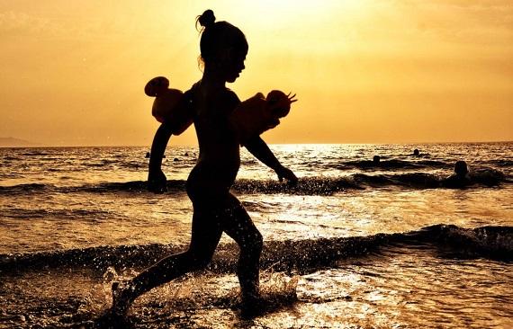 Fetita surprinsa in timpul unui apus de soare la mare