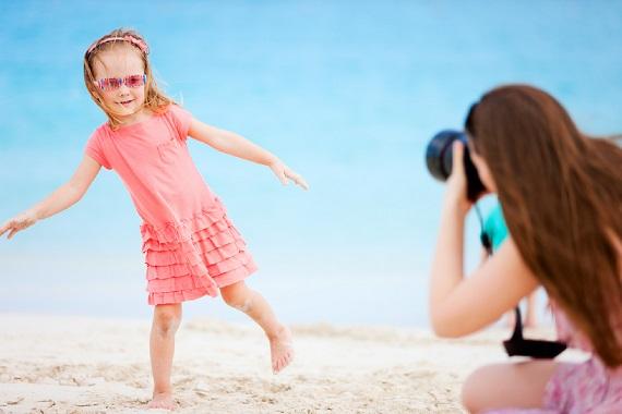 Mama ce isi pozeaza fetita pe plaja