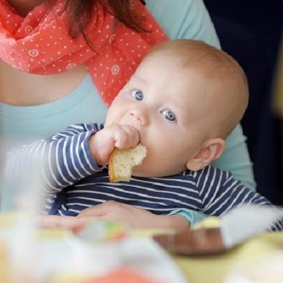 Bebelus ce tine in mana paine alba si sta in bratele mamei