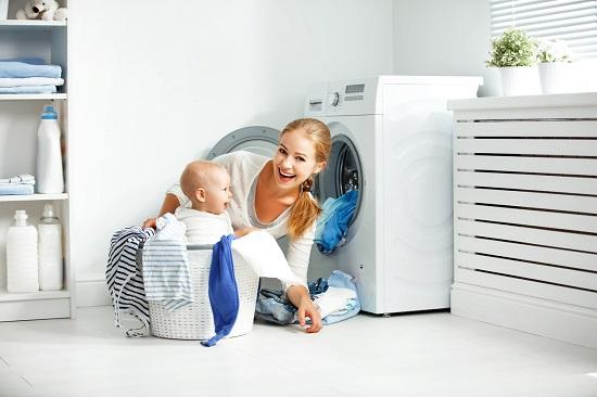 Mama ce se pregateste sa puna rufele la spalat si bebelus aflat in cosul de rufe