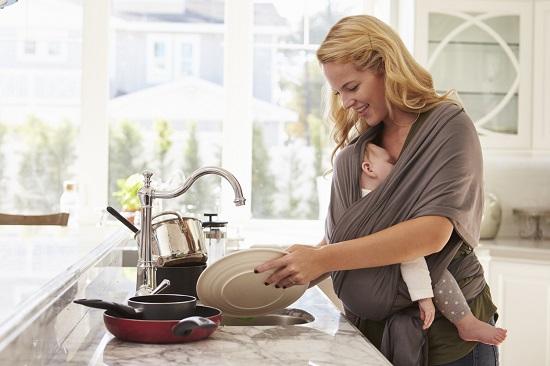 Mama ce spala vasele cu un bebelus in marsupiu