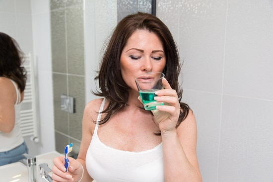 Femeie ce se clateste cu apa de gura
