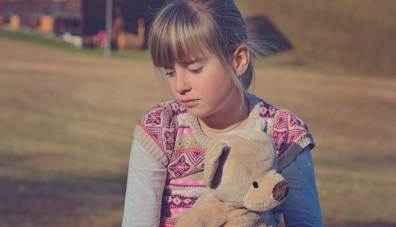 Fetita foarte trista, cu un ursulet in brate