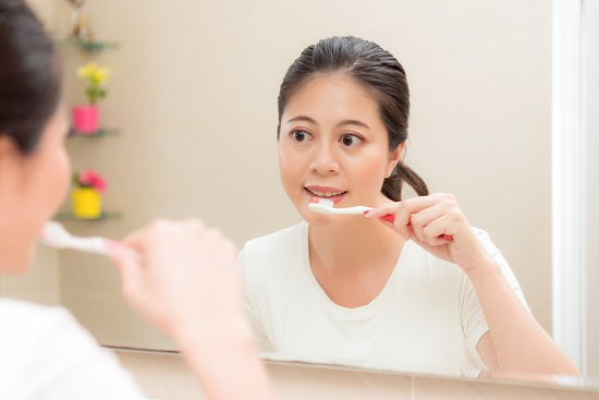 Femeie ce se spala pe dinti in fata oglinzii