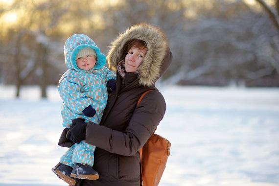 Femeie ce tine un bebelus in brate, stand pe-afara, in sezonul rece