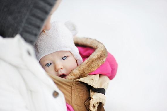 Mama ce isi tine bebelusul in brate, cand sunt pe-afara, iarna