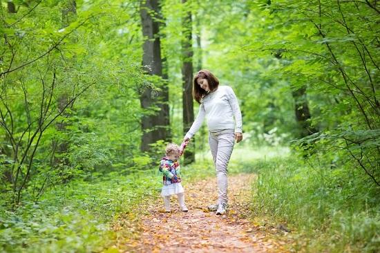 Mama insarcinata la plimbare prin padure, alaturi de fetita ei