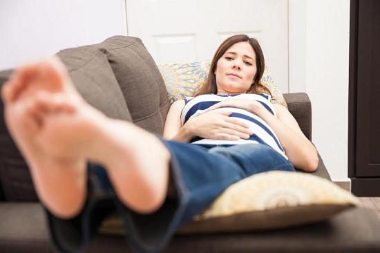 Femeie insarcinata ce sta intinsa, cu picioarele ridicate pe o perna