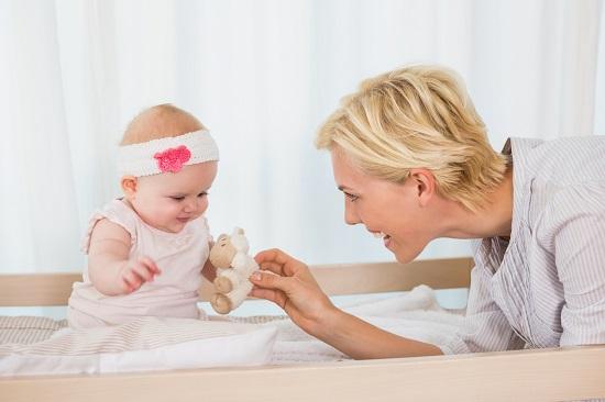 Mama ce ii arata bebelusei ei o jucarioara