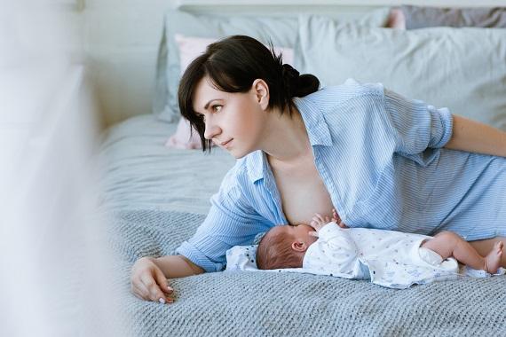 Mama ce isi alapteaza bebelusul stand pe pat