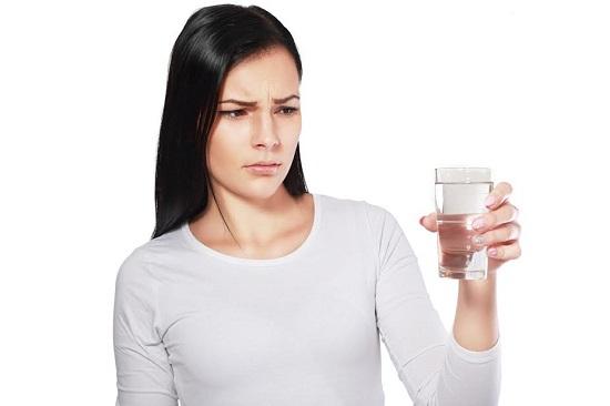 Fata ce se uita la un pahar cu apa