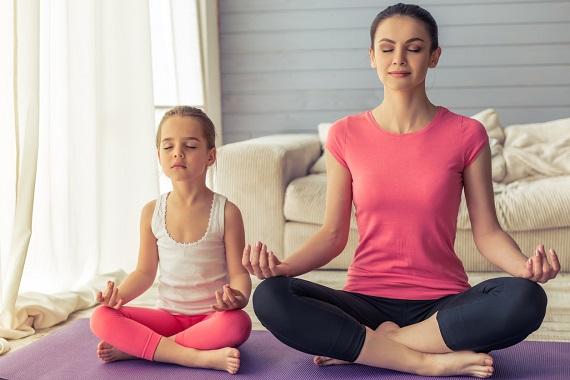 Mama si  fetita ei stau in pozitie de yoga