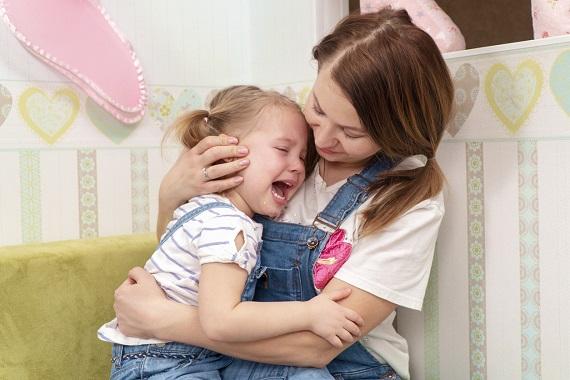 Mama ce isi consoleaza fetita care plange
