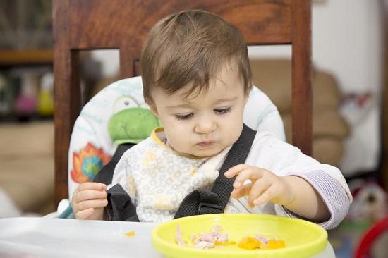Bebelus in scaunelul sau, ce incearca sa se hraneasca singur