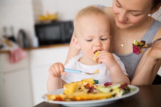 Mama se uita cum al ei bebelus se hraneste singur