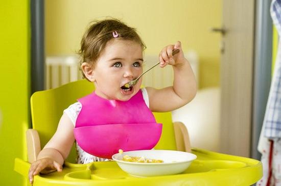 Fetita in scaunel special de bebelusi, ce incepe sa se hraneasca singura cu lingura