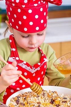 Fetita ce adauga miere in muesli