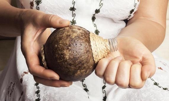 Femeie ce isit toarna in palma ulei de cocos