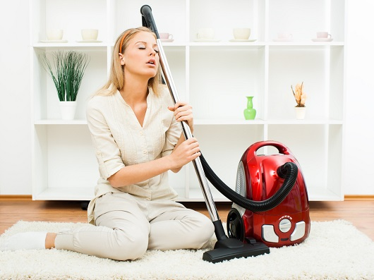 Femeie obosita, alaturi de aspirator
