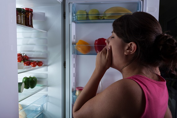 Femeie aproape adormita, in fata frigiderului