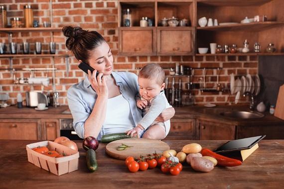 Mama ce vorbeste la telefon in timp ce este cu bebelusul in bucatarie
