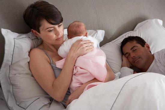 Mama ce are grija de bebelus, in timp ce tatal doarme