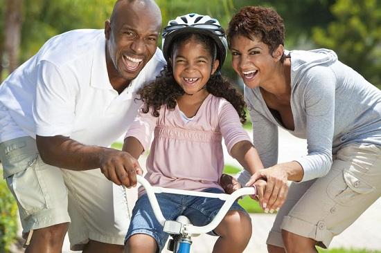 Parinti alaturi de fetita lor, ce se pregateste sa mearga cu bicicleta