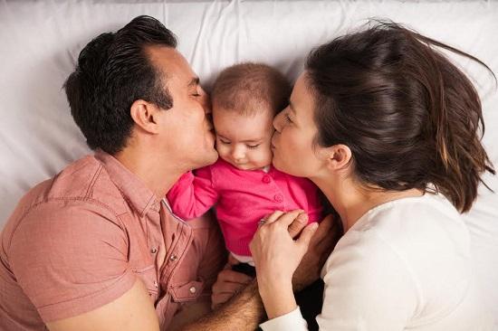 Mama si tata ce isi saruta copilul