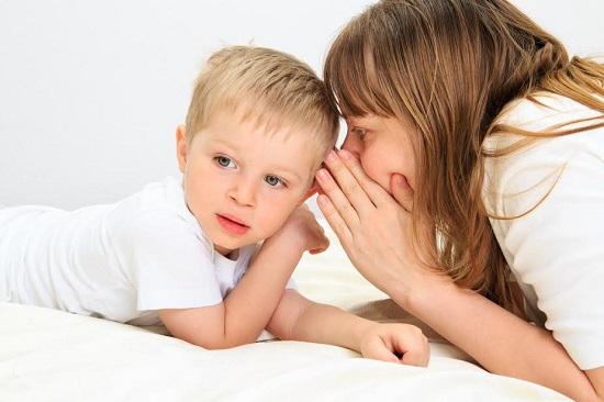 Mama ce ii vorbeste la ureche baietelului ei