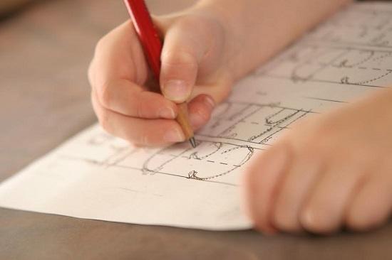 Copil ce contureaza litere punctate