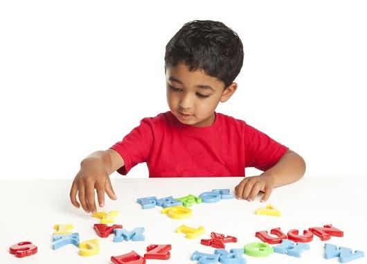 Baietel ce se joaca cu litere magnetice