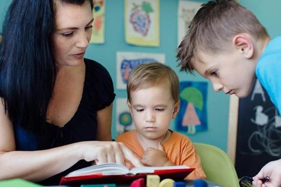 Mama le arata copiilor ceva dintr-o carte