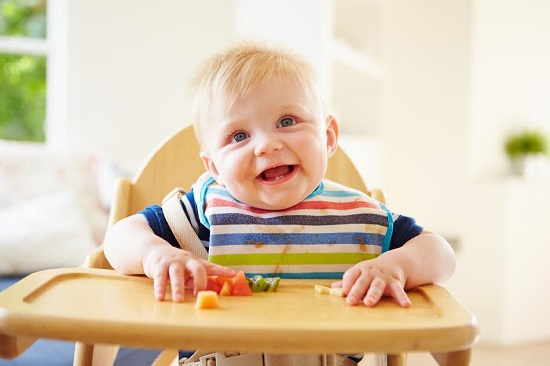 Bebelus ce sta in scaunelul special, la masa