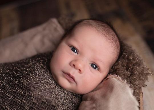 Bebelus ce sta pe un pat